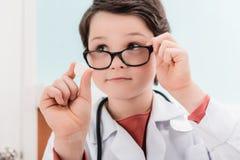 Pojkedoktor i glasögon som rymmer preventivpilleren i hand Arkivbild