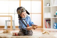 Pojkedrömmar för liten unge är en flygare och lekar med leksakflygplan som sitter på golv i barnkammarerum Arkivfoto