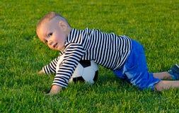 Pojkedykning på en fotbollboll arkivbilder
