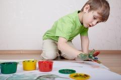 pojkefärg tecknar fingrar hans målarfärger royaltyfria bilder