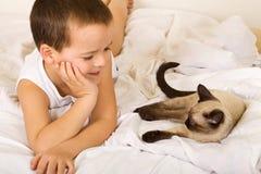 pojkeföretag som little tycker om hans kattunge royaltyfria bilder