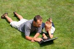pojkefader hans working för bärbar dator s Arkivfoto