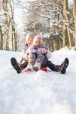 pojkeflicka som åka släde snöig skogsmark Fotografering för Bildbyråer
