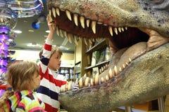 pojkeflicka som ser den mun öppnade tyrannosaurusen Arkivfoto