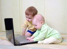 pojkeflickabärbar dator little som använder Royaltyfri Fotografi