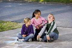 pojkeflickor skrattar framställning arkivfoto