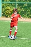 Pojkefotbollspelare med bollen på fotbollfält arkivfoto