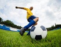 Pojkefotbollspelaren slår fotbollbollen Fotografering för Bildbyråer
