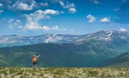 Pojkefotvandrare med ryggsäckpunkter till bergmaximumet royaltyfria bilder