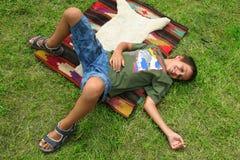pojkegräsläggande royaltyfri foto