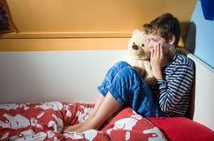 Pojkegråt på hans säng Royaltyfri Fotografi