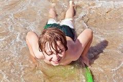 pojkegyckel har surfingbrädan Arkivfoto