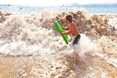 pojkegyckel har surfingbrädan Arkivbilder