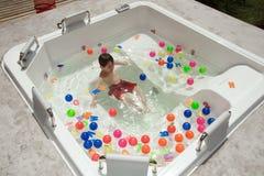 pojkegyckel som har bubbelpoolen Arkivfoto