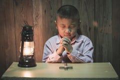 Pojkehänder som ber med ett heligt kors i mörkret och med lampan bredvid, barn som ber för gudreligion arkivfoto