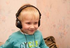 pojkehörlurar som littening musik till royaltyfria foton