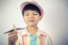 Pojkehandelsresande som rymmer en leksaknivå för världslopp Arkivbild
