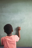 Pojkehandstil med krita på greenboard royaltyfri bild
