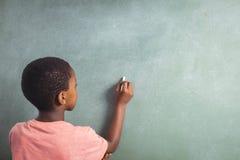 Pojkehandstil med krita på greenboard i skola arkivbild