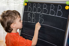 Pojkehandstilbokstäver som lär det smarta barnet för proccesson Fotografering för Bildbyråer