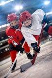 Pojkehockeyspelare som behandlar pucken på is royaltyfria foton