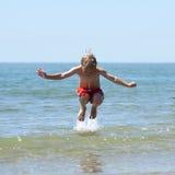 pojkehopp över wave Arkivfoto