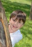 Pojkehuvud bak träd Royaltyfri Bild