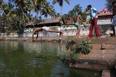 pojkeindier hoppar behållarevatten royaltyfria bilder
