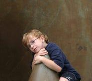 pojkeinnehållsleende Arkivbild