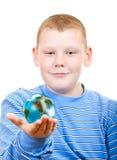 Pojkeinnehav ett jordklot i form av planet Royaltyfri Foto