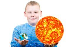 Pojkeinnehav sunen och det terrestrial jordklotet. Royaltyfri Bild