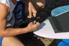 Pojkeinställning - upp hans vita bräde, innan att surfa i havet royaltyfri bild