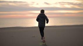Pojkekörningen längs stranden på solnedgången arkivfilmer