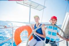 Pojkekapten med hans syster ombord av seglingyachten på sommarkryssning Resa affärsföretaget som seglar med barnet på familjen arkivbild