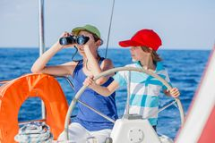 Pojkekapten med hans syster ombord av seglingyachten på sommarkryssning Resa affärsföretaget som seglar med barnet på familjen royaltyfri foto