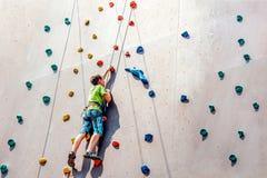 Pojkeklättraren klättrar på ett konstgjort torn som övervinner upp hinder på hans väg royaltyfri bild