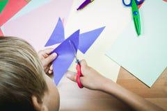 Pojkeklipp färgade papper med sax på tabellen Arkivbilder