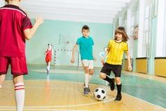 Pojkeklockas slagboll som spelar fotboll i sportkorridor Arkivfoton