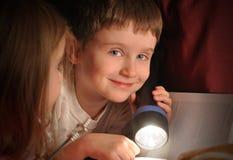 Pojkeläsebok på natten med ficklampan Arkivfoton