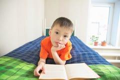 Pojkeläsebok som ligger på säng, barn utbildning, barnstående med boken, utbildningsbegrepp, intressant berättelsebok Arkivbilder