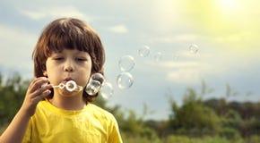 Pojkelek i bubblor i solig sommardag royaltyfri foto