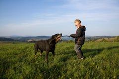 Pojkelek med hunden Arkivbild