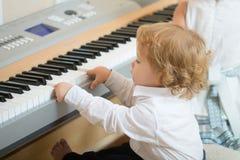 Pojkelek på digitalt piano royaltyfri fotografi