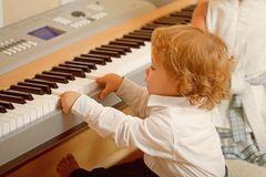 Pojkelek på digitalt piano royaltyfria foton