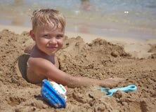 Pojkelek på thstranden Arkivbild