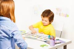 Pojkelekar i den framkallande leken som pekar på kalendern Arkivbilder