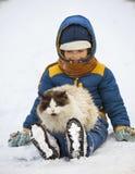 Pojkelekar med en katt utomhus Arkivbild