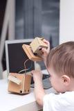 Pojkelekar med roboten på ett vitt tabellhem arkivfoton