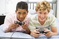 pojkelekar som leker den tonårs- videoen Arkivfoton