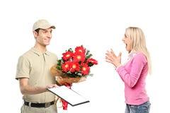 pojkeleveransen blommar holdingen förvånade kvinnan Royaltyfria Bilder